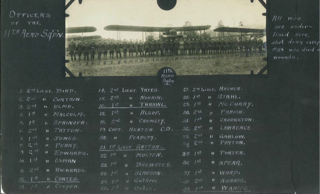A page from a photo album showing a single photo, a line up of officers in front of DH-4s, with a number written under each man from 1 to 39. Underneath, in white ink on the black paper of the album, are the identifications of each man.