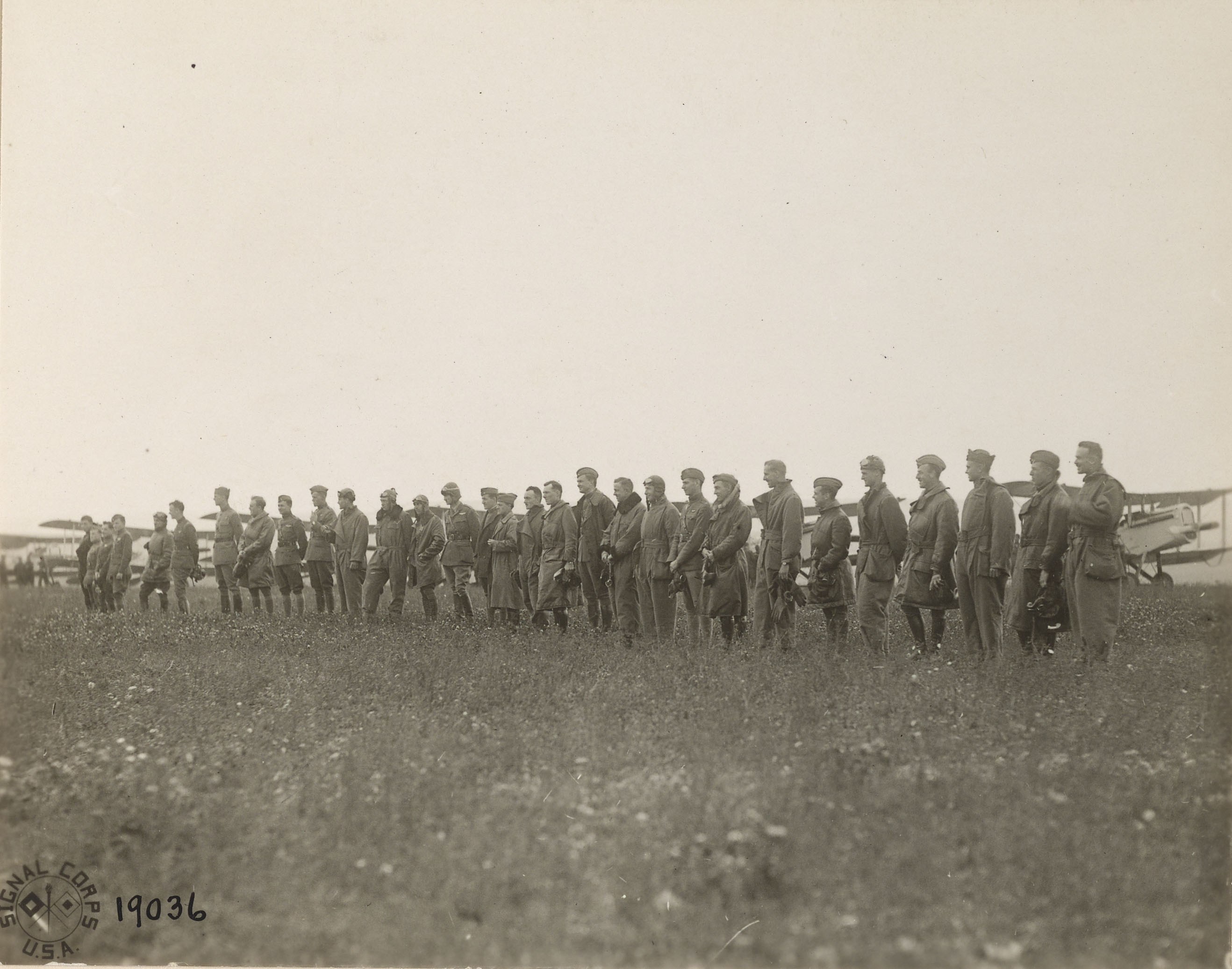 A line of about thirty men in front of a line planes on the horizon.