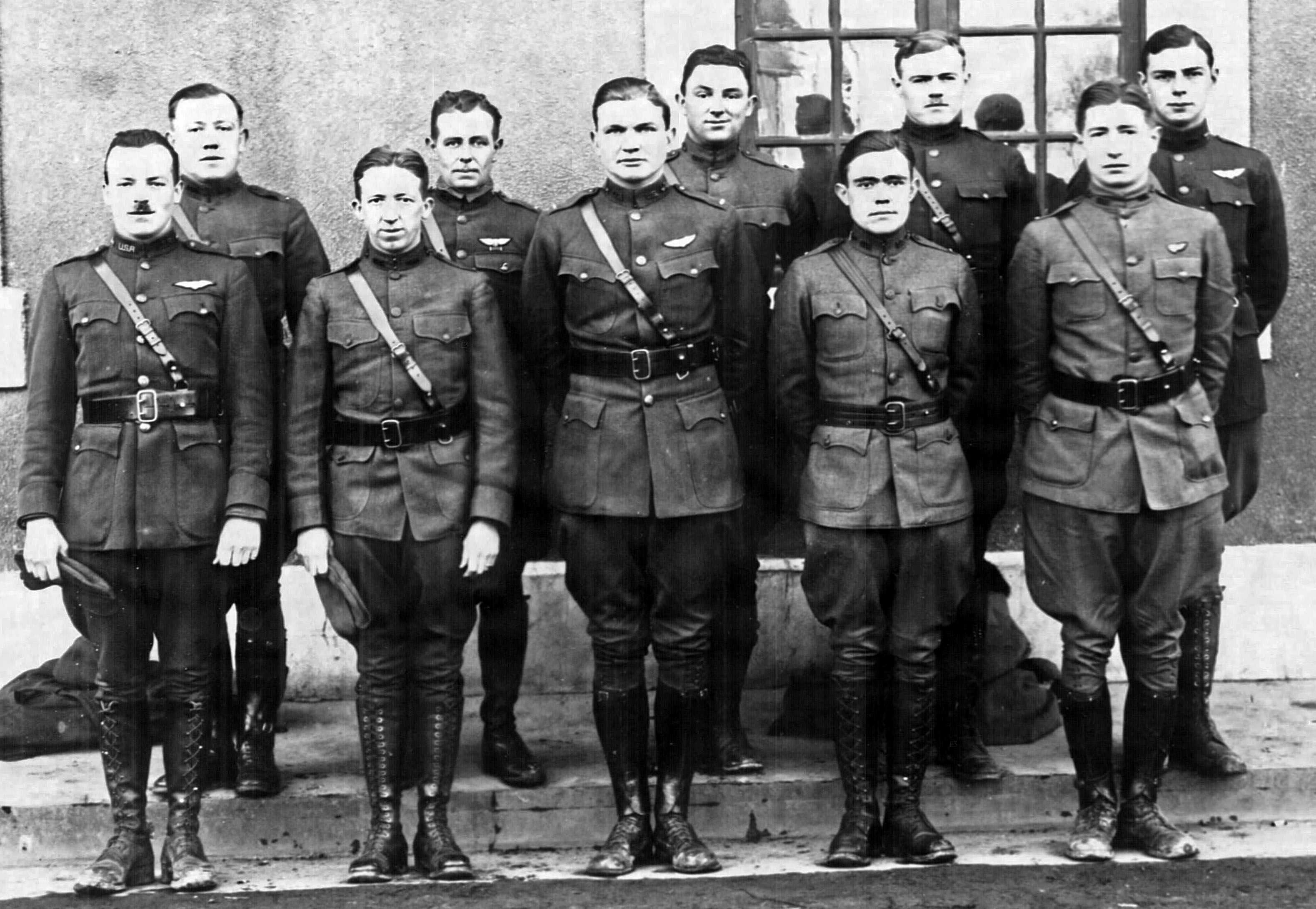 A photo of ten men in uniform, posing rather stiffly in two rows before a stone house with mullioned windows.