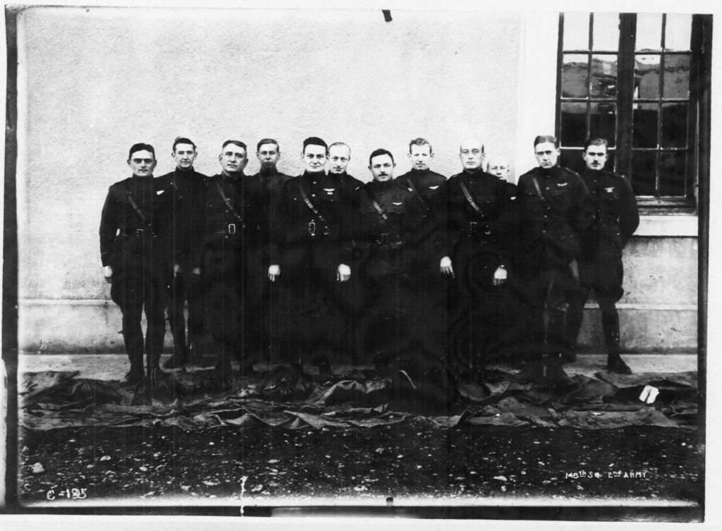 Photo of twelve officers standing in front of a white stone building.