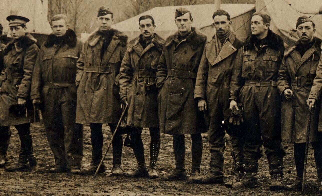 A detail from the preceding sepia photo of a long line of men; this detail shows the eight men from the middle of the row who appear to be officers.