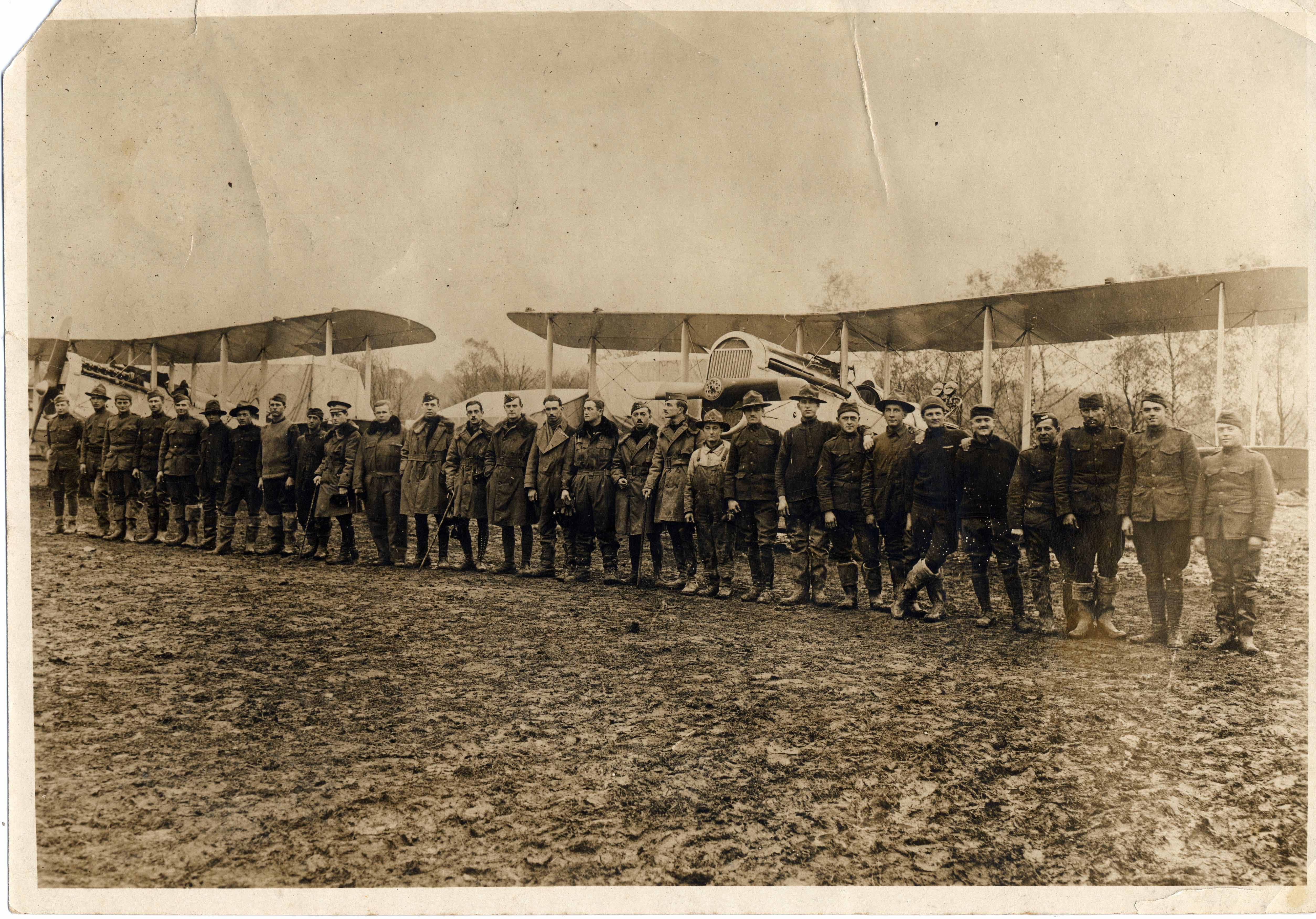 A sepia-colored photo of a diagonal line of about 30 men in front of DH-4 planes. Some of the men are more casually dressed and appear to be enlisted men; a group of about 9 men in the middle of the line appear to be officers. The foreground appears to be a muddy field.