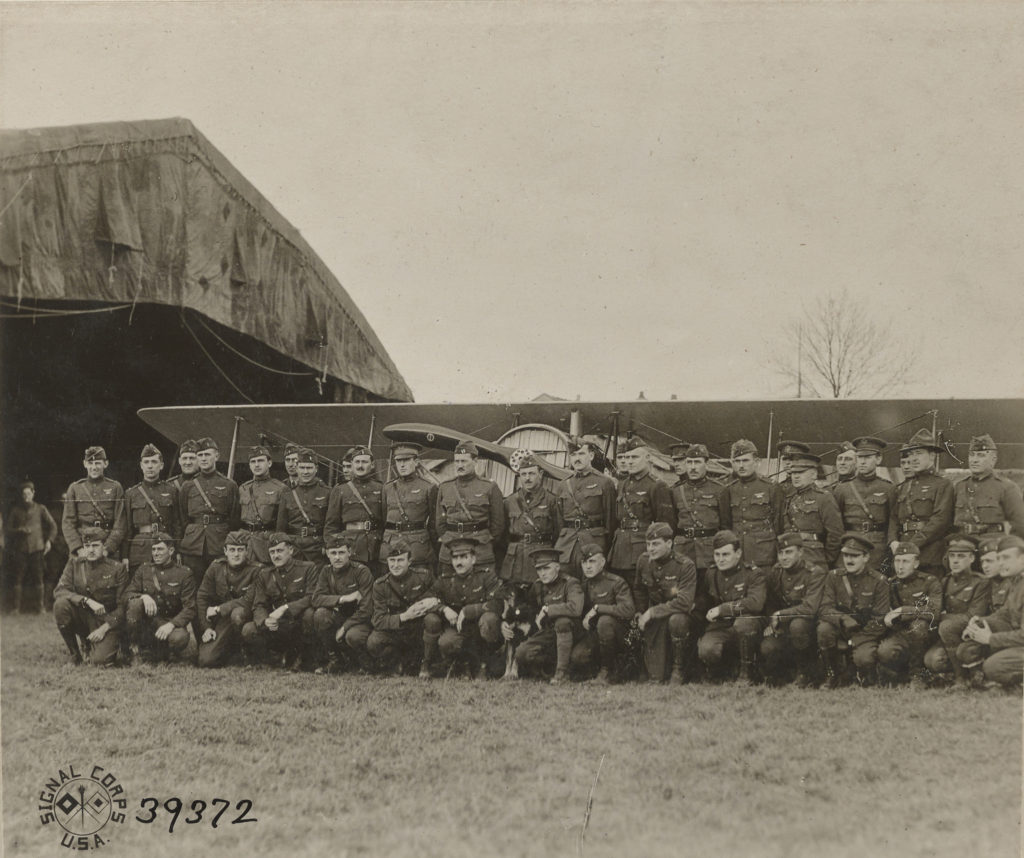"""A photo of two rows of men in uniform, nearly all with pilot's wings on their chests, standing in front of an airplane. The photo is stamped """"Signal Corps U.S.A."""" and the number 39372 has been written on it in ink."""
