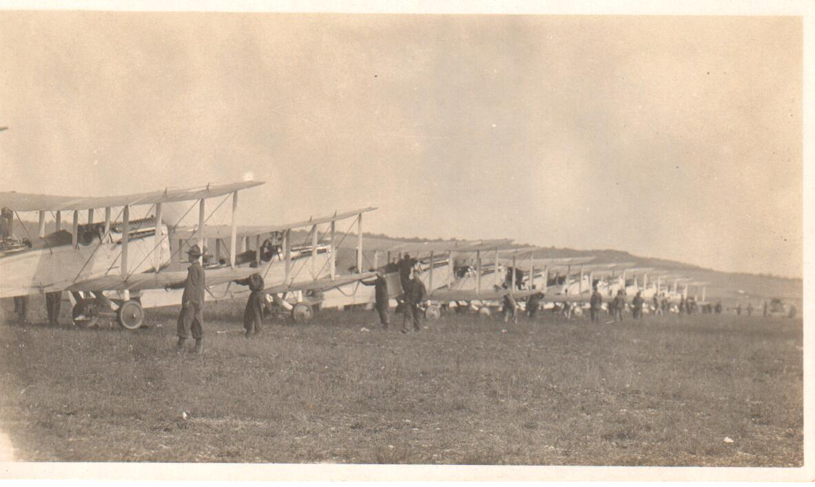 About fifteen DH-4s lined up, receding in perspective from close up at left to barely visible at right.