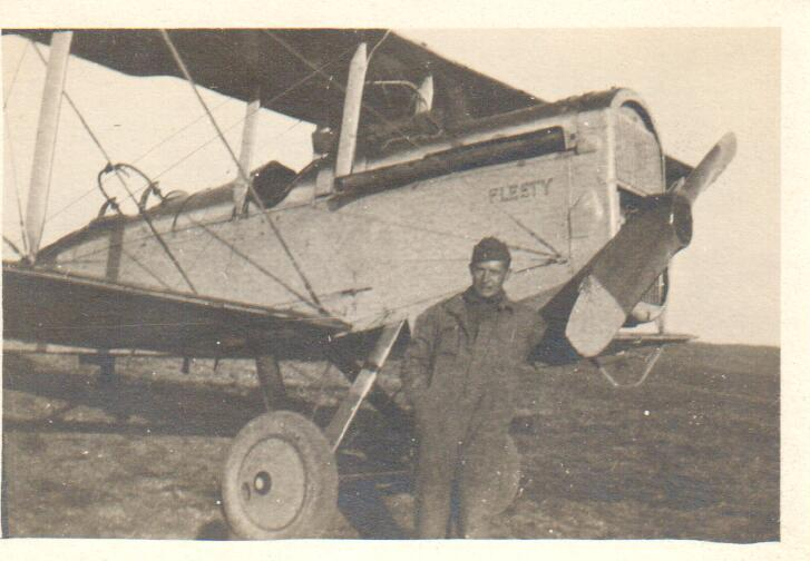 """A man dressed in a mechanic's suit standing next to the propeller of a DH-4 that has """"Fleety"""" painted on it."""