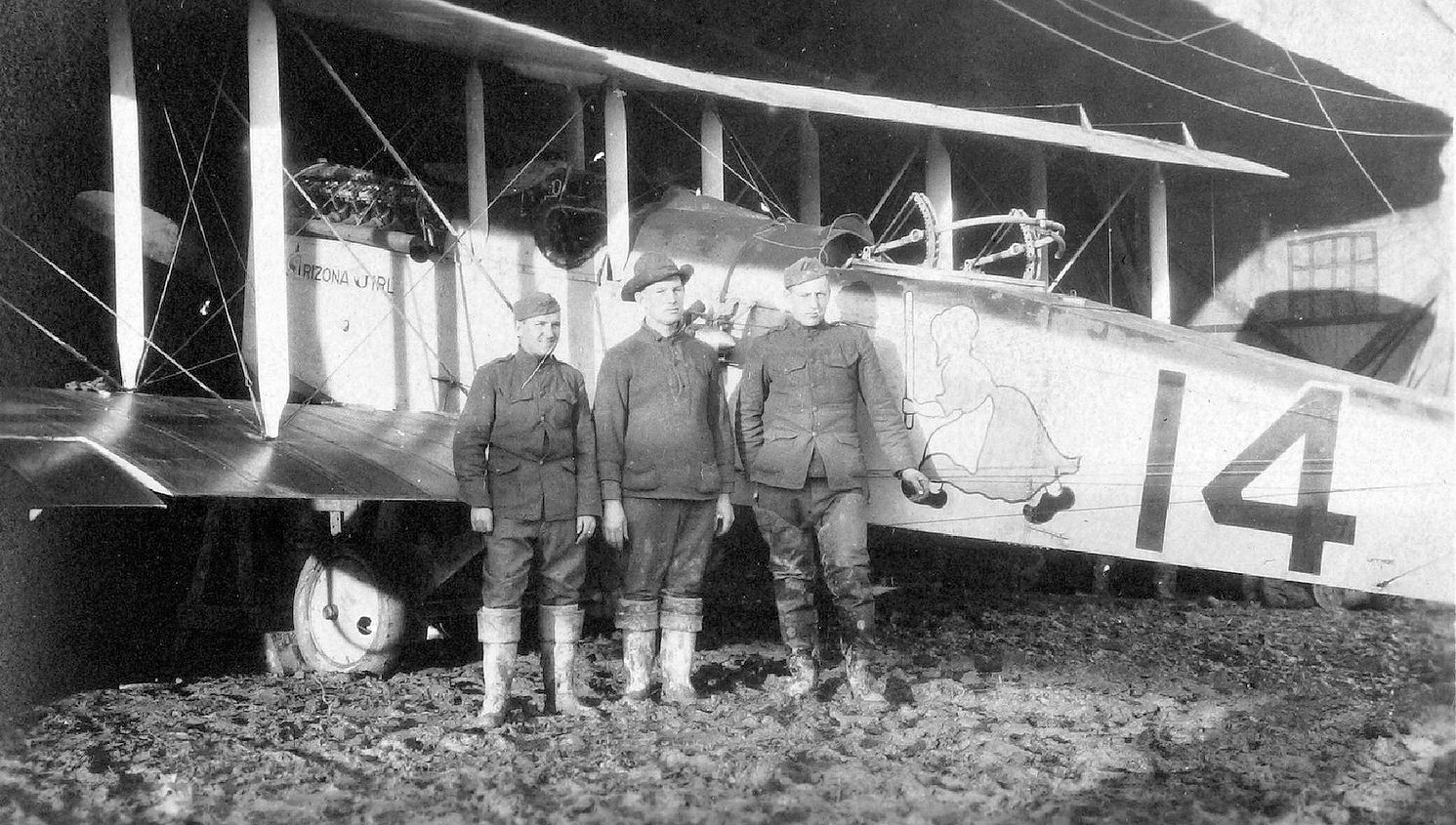 A photo of three men standing in front of plane that has the number 14 on it.