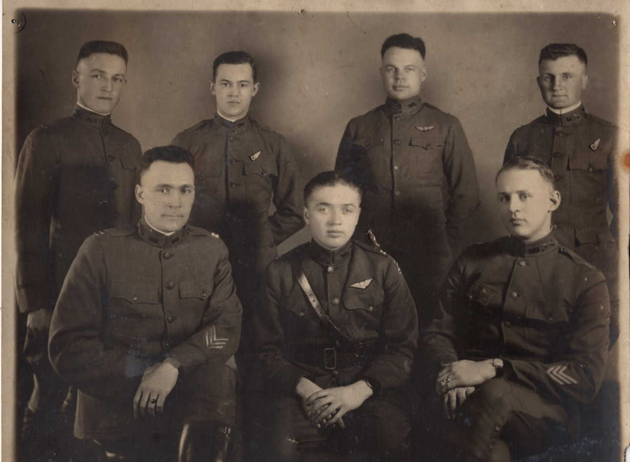 A photo of seven men in uniform, four standing and three seated.