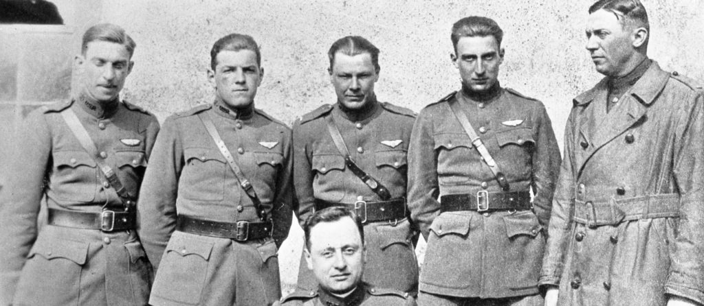 A photo of five men in uniform standing, in front of a sixth man, apparently seated.