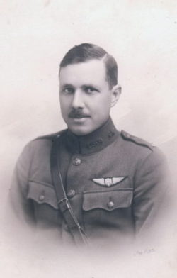 Formal portrait, head and shoulders, of a hatless young man in uniform, wearing a Sam Browne belt, with a pilot's wings above his left pocket.