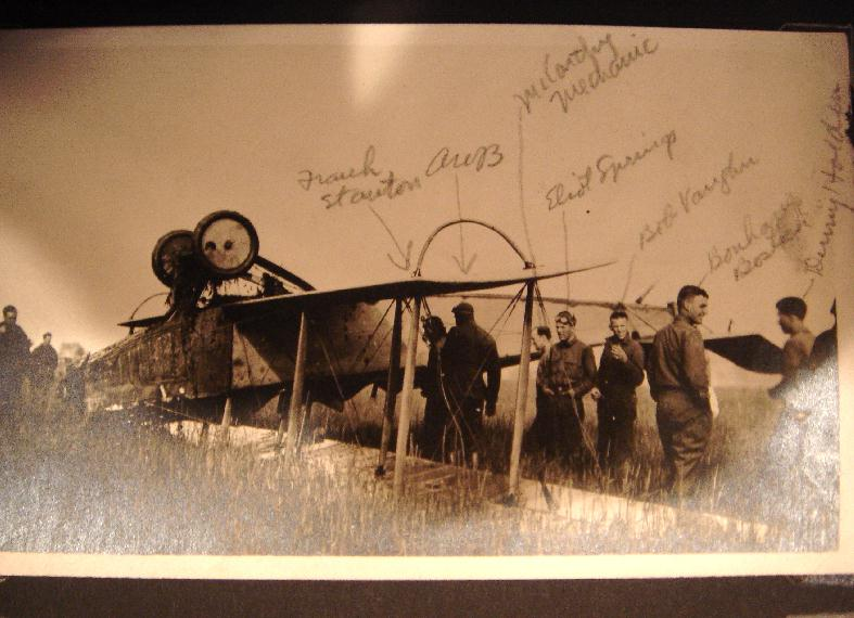 Photo of an upside down plane in a field, with a number of men inspecting it. Names have been written in identifying, among others, Springs, Vaughn, and Bostick.