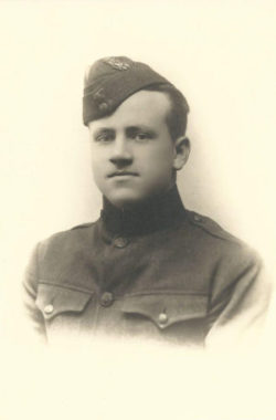 Photo, head and shoulders of a young man in uniform looking into the camera.