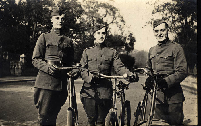 Photo of three men in uniform standing next to bicycles on a leafy street.