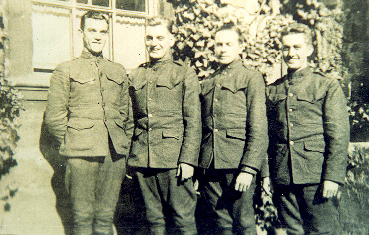 Four hatless men in military tunics standing before ivy-covered walls.