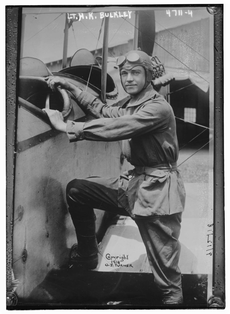"Photo of a man in a flying suit with goggles on his forehead apparently getting ready to climb into a two-seater plane. At the top is written ""Lt. H. K. Bulkley."" Towards the bottom is written ""Copyright 1918 O. J. Turner."""