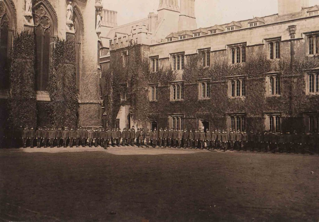 Photo of a long line of uniformed men standing in front of the towering, ivy covered walls of gothic buildings; they are in the northeast corner of the front quadrangle of Exeter College, Oxford.