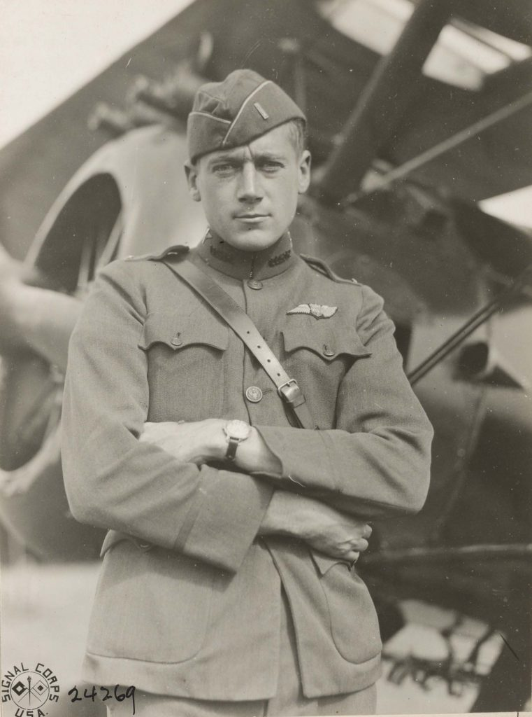 Close-up three quarter photo of Callahan in uniform in front of an airplane.