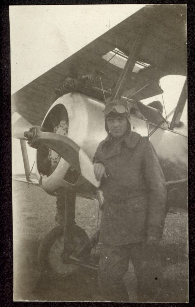 Photo of man in flying helmet with goggles standing in front of a Sopwith Camel.
