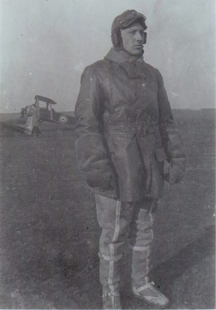 A man in flying clothes and leather flying helmet in the foreground, with a Sopwith Camel in the background.
