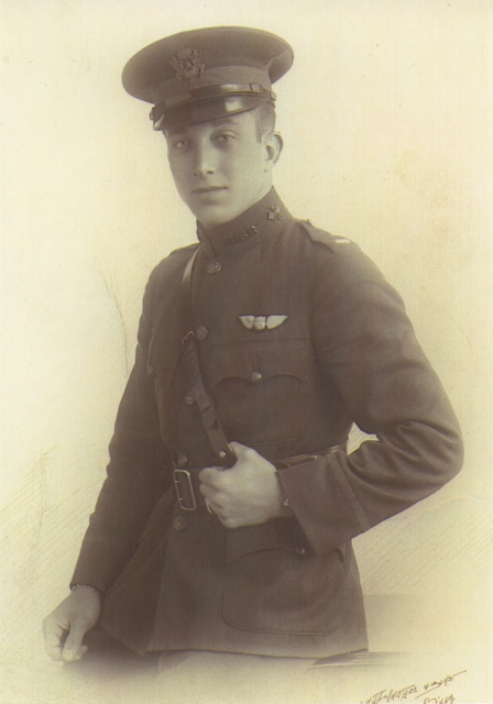 Three quarter formal studio photo of young man in uniform with pilot's wings over his left breast pocket and wearing a peaked officer's cap.