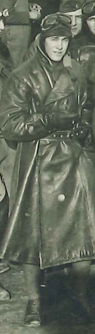 Full-length photo of man in leather flying coat and helmet, evidently a detail from a larger photo.