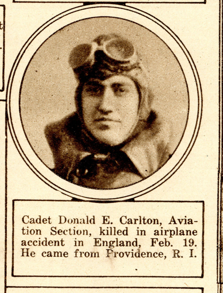 "From a somewhat yellowed newspaper, a photo of Carlton's face, in flying helmet with goggles on forehead, in oval frame, captioned ""Cadet Donald E. Carlton, Aviation Section, killed in Airplane accident in England, Feb. 19. He came from Providence, R.I."""