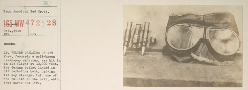 """A photo of four bullets from a cartridge belt next to a pair of aviator goggles pasted onto a piece of archives paper with the notation """"from American Red Cross,"""" a catalogue number, and a description of the photo focussed on the cartridge belt."""