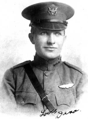 Formal photo of head and bust of a young man in uniform with a peaked cap, Sam Browne belt, and wings over his left breast pocket.