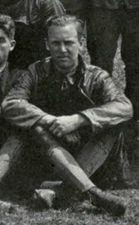 Photo of a man sitting on the ground with legs crossed; it is evidently cropped from a group photo.