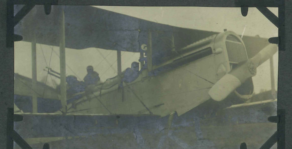 Close up photo of a DH-4 showing front of fuselage and wings, with pilot in cockpit and man behind him manning guns.