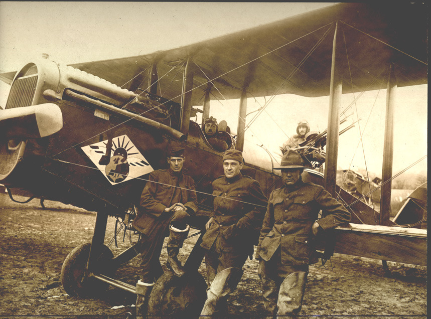 A photo of a DH-4 with Devery in the cockpit and Henry Irving Jenks acting as gunner. There are also three men in the foreground leaning against the plane.