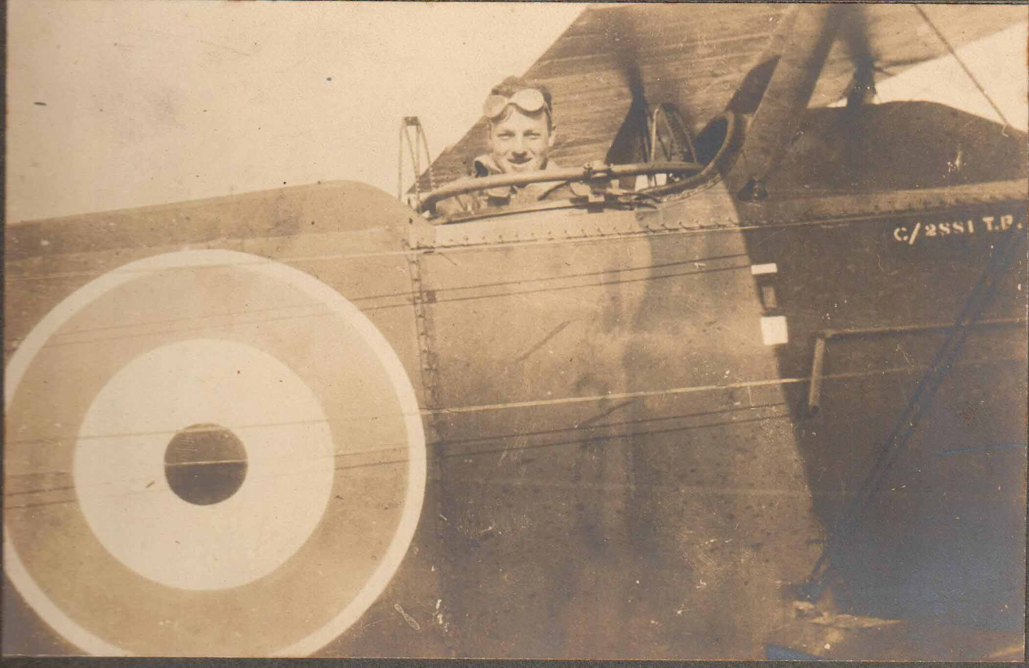 Close up photo of a plane with a man's head visible in the cockpit.