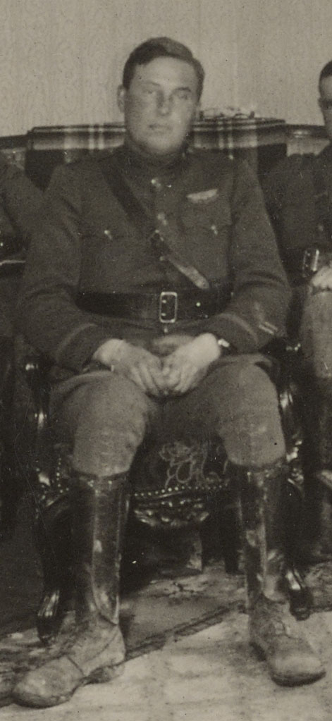 Foss, in uniform, with muddy boots,looking tired and pensive, sitting in rather ornate chair.
