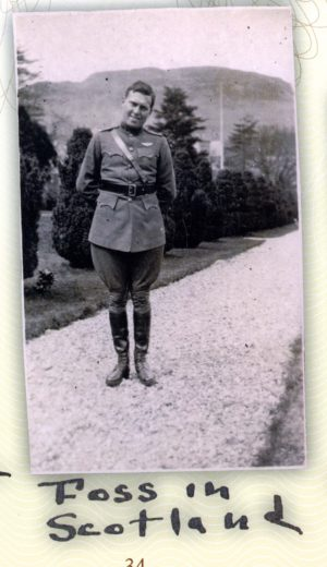 Foss in uniform, with pilot's wings above his left breast pocket, standing on what appears to be a gravel walk with a background of evergreens and a hill.