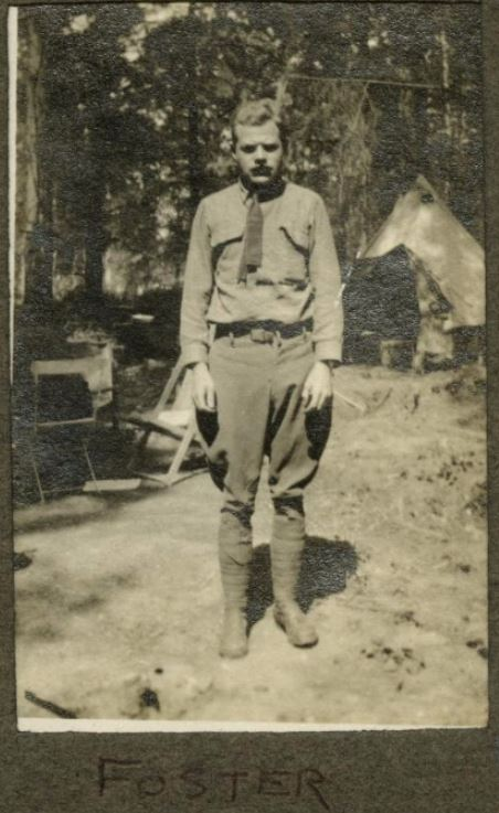 "A photo labelled ""Foster"" pasted into an album showing a mustached man standing before a tent."