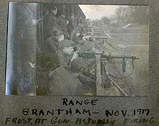 "A poorly reproduced black and white photo showing a line of men at machine guns receding into the distance, with the caption ""Range Grantham, Nov. 1917, Frost at Gun actually firing."""