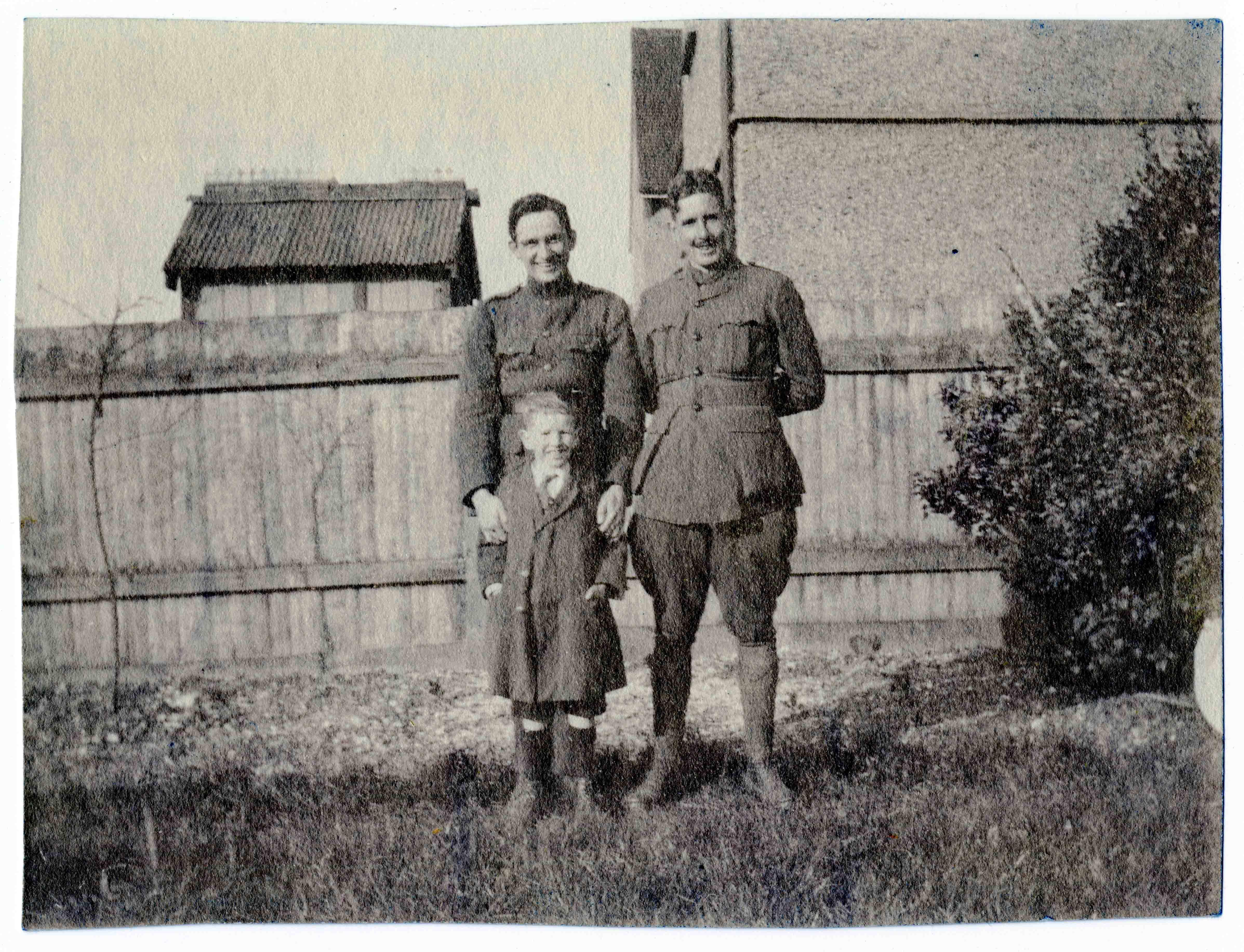 A photo of two men in uniform, but without pilots' wings, outdoors, apparently in the backyard of a house, standing in front of a boy, about seven years old.