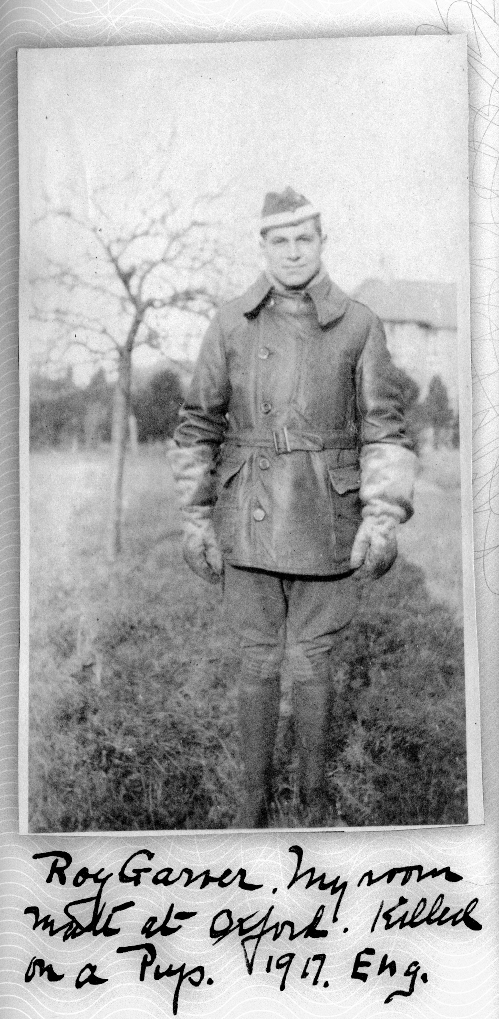 """Photo of a man wearing an R.F.C. cap with a white band, and a flying jacket and gauntlets. A handwritten caption reads """"Roy Garver. My room mate at Oxford. Killed on a Pup. 1917. Eng."""""""