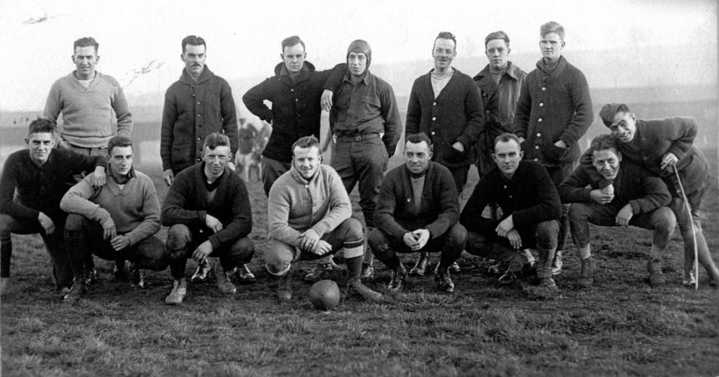 An informal shot of fifteen men ready to play football.