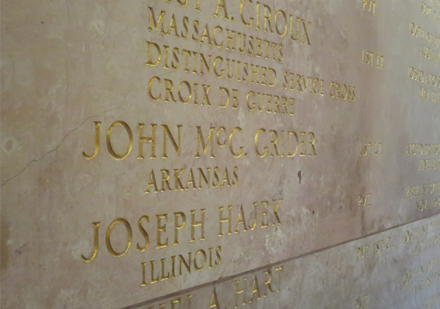 "An oblique photo of a wall with names carved into it and gilded; prominent in the center is ""John McG. Grider Arkansas."""