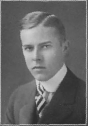 Head and shoulders photo of a serious looking young man in suit and tie.