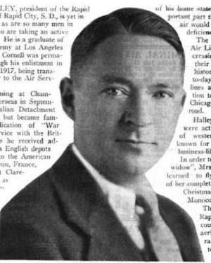 Photo of man from shoulders up, wearing suit and tie, surrounded by text; photo evidently taken from a magazine or the like.
