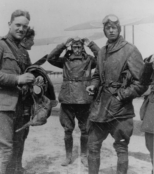 Four pilots (with part of a fifth pilot just visible) in uniform apparently preparing to fly.