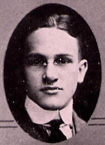 Yearbook photo of Hamilton showing his face and a high collar and tie. He is apparently wearing rimless glasses.