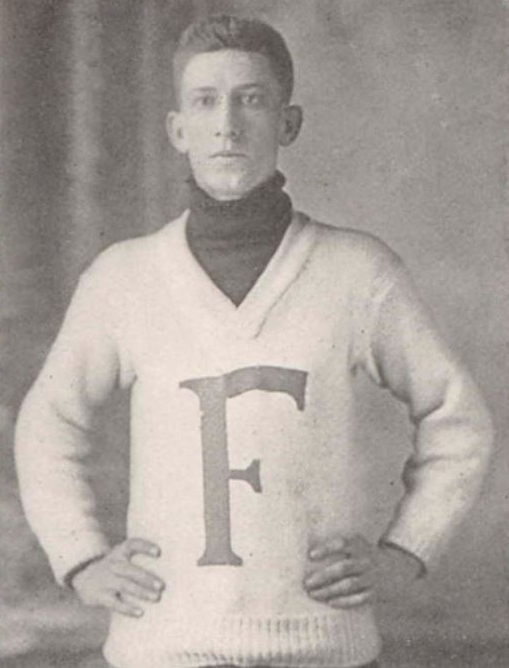 "A photo from the waist up of a man wearing a white sweater with a large ""F"" on it."