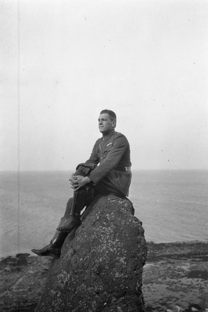 Man in uniform sitting on a rock with beach and ocean in back ground.