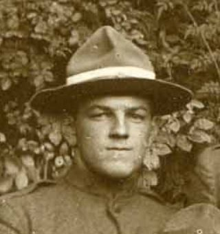 Photo of man (face and shoulders) wearing a campaign hat against a background of ivy leaves.