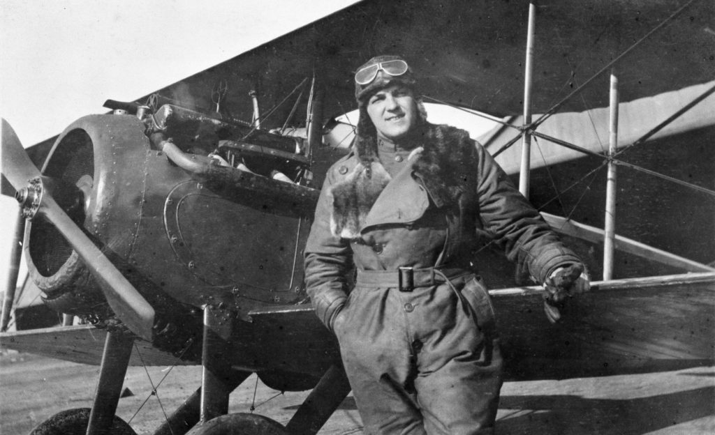 A pilot in flying clothes and helmet with goggles, in front of a Spad VII.