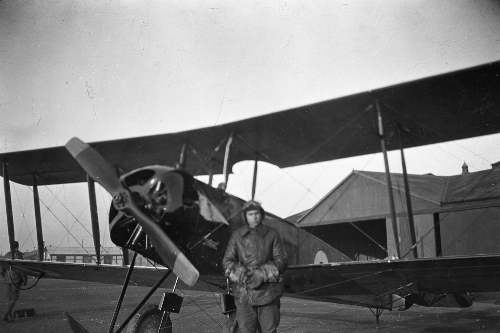 Black and white photo of a plane (an Avro) in front of a large hangar, with a man in leather flying clothes and helmet standing in front of the plane.