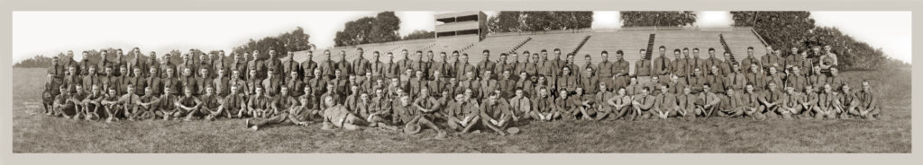 A wide angle picture of approximately 120 uniformed men in four rows in front of outdoor bleachers.