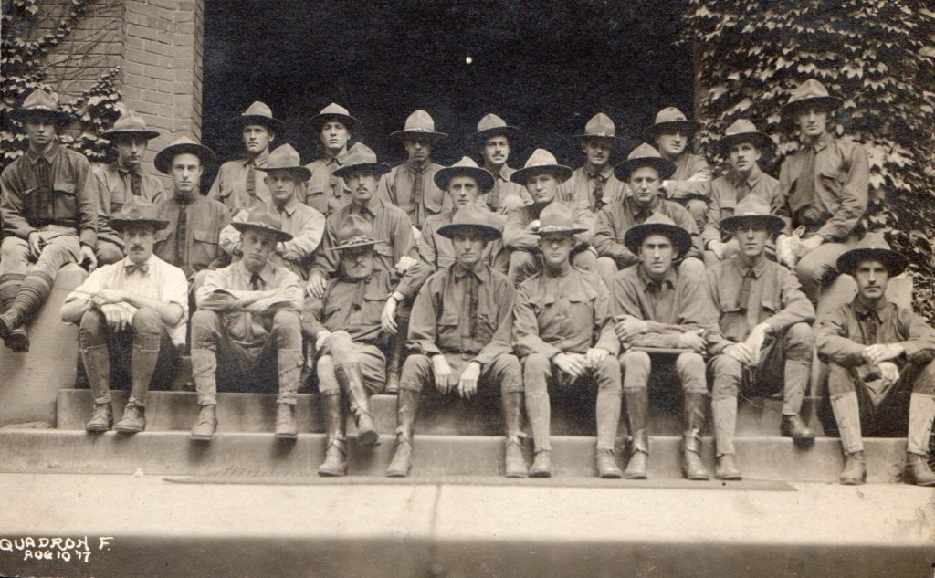 """Photo of twenty-four men wearing campaign hats seated in three rows on the steps of a building with ivy covered walls. Written in the lower left corner is the notation """"Squadron F. august 10 '17."""""""